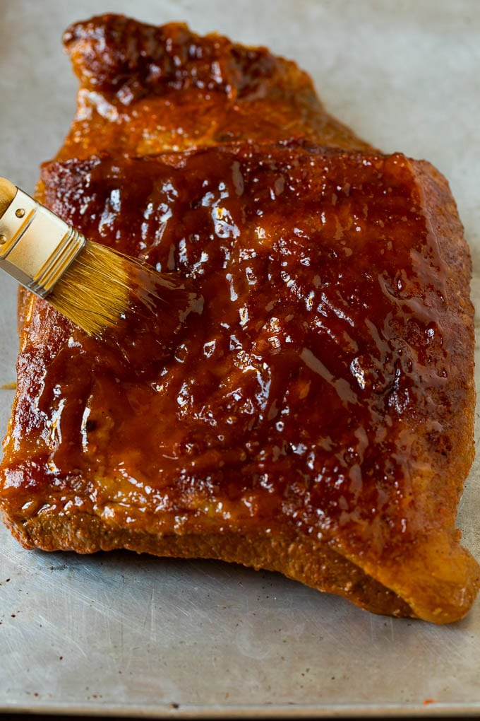 BBQ sauce being brushed over a piece of brisket.