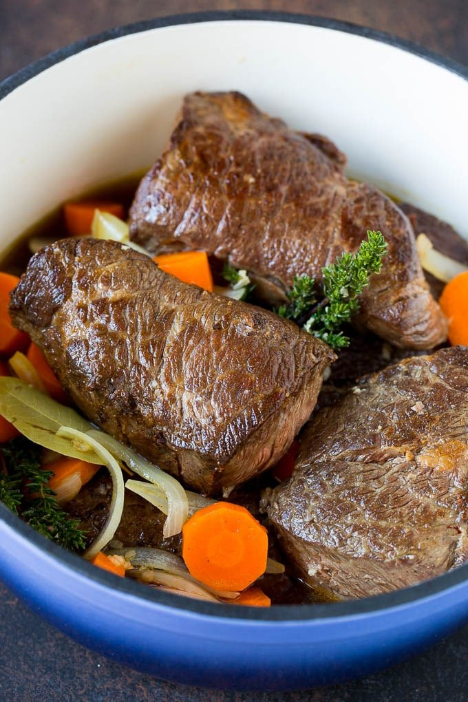 Short ribs with carrots and onions in a pot.
