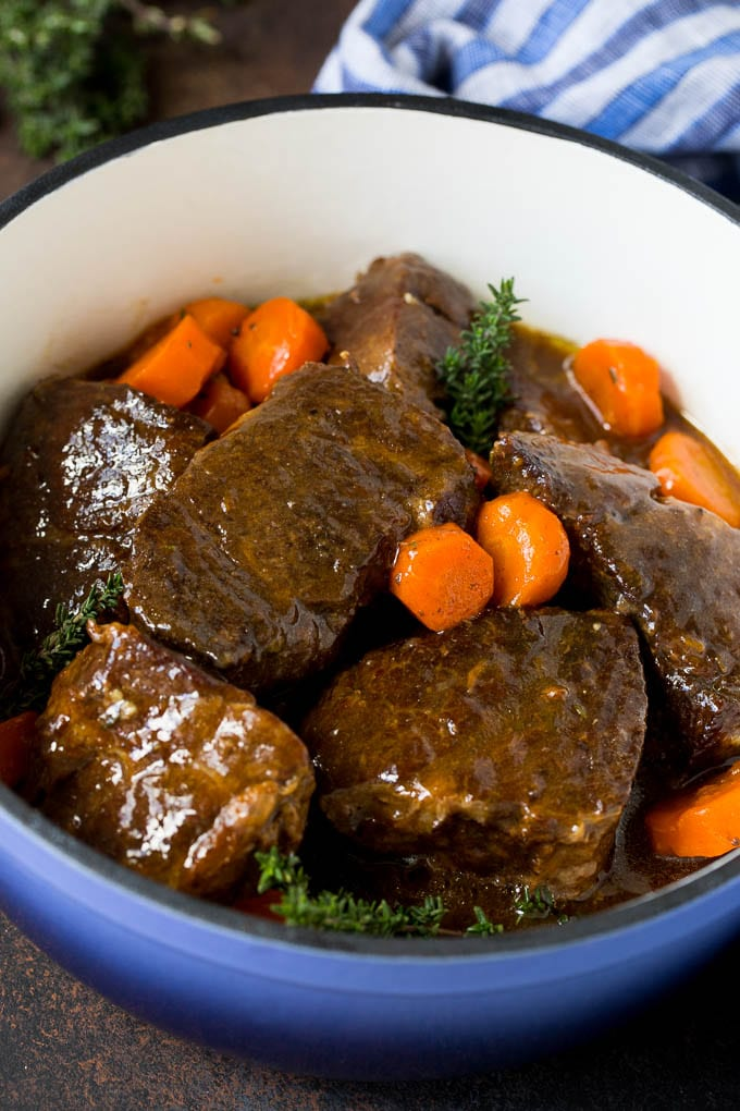 Braised short ribs with carrots in a blue pot, garnished with fresh thyme.