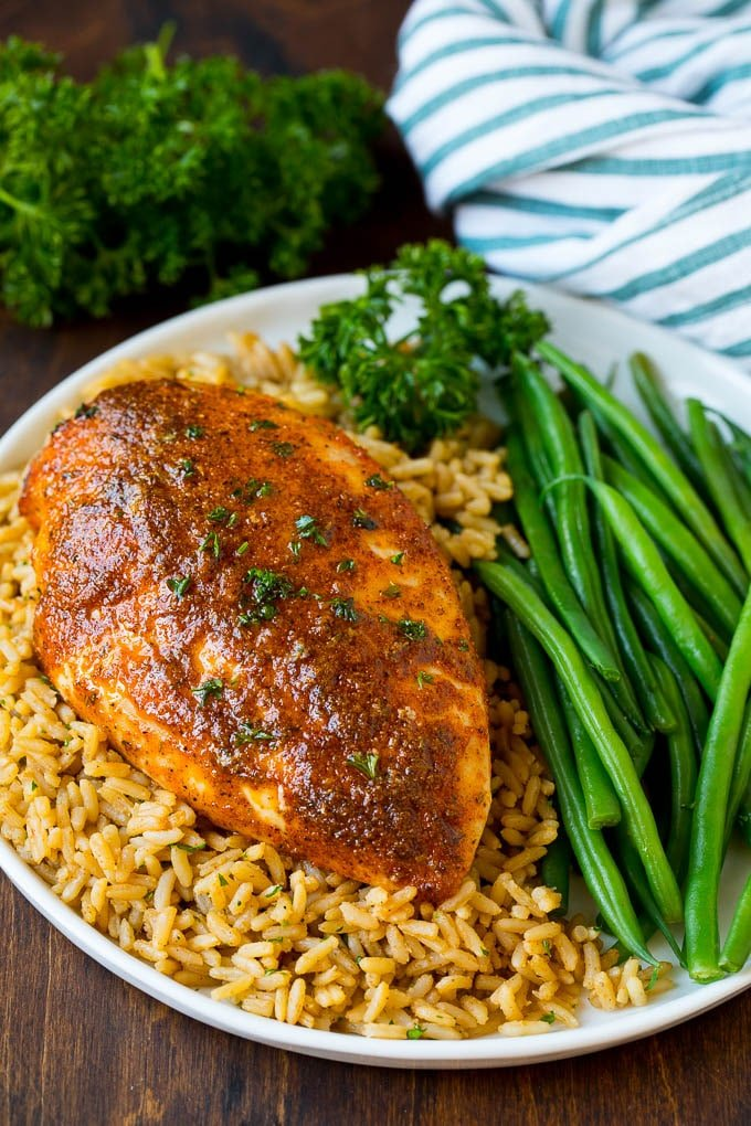 Cajun chicken served over rice with a side of green beans.
