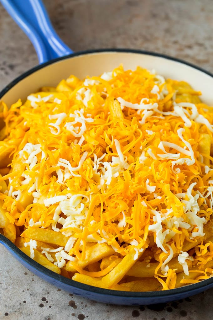 A skillet of fries topped with shredded cheese.