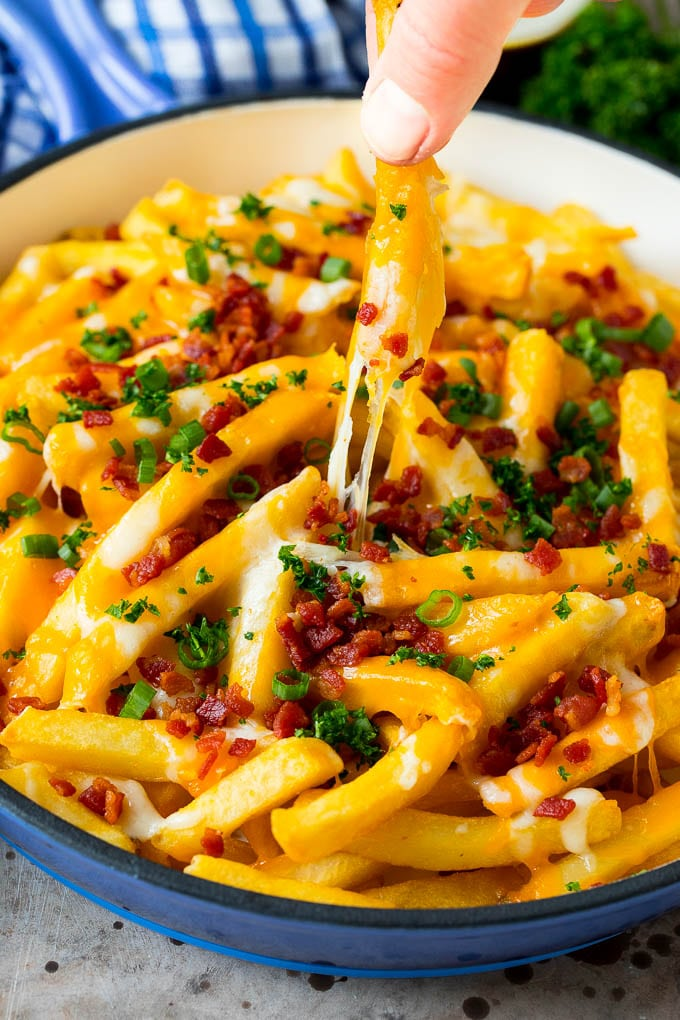 A skillet of cheese fries with bacon, and a hand reaching for one.