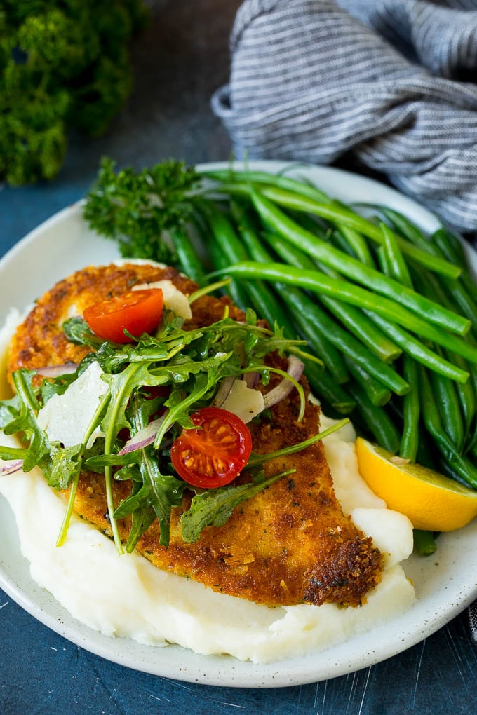 Chicken milanese served over mashed potatoes with a side of green beans.