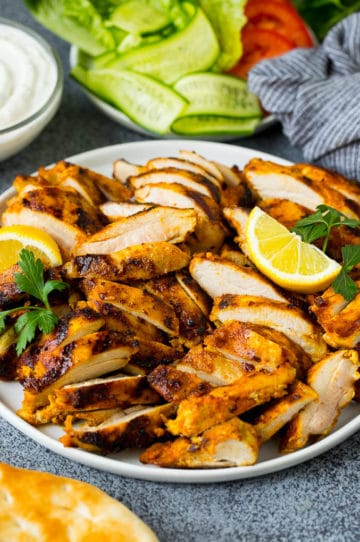 Sliced chicken shawarma garnished with parsley and lemon.