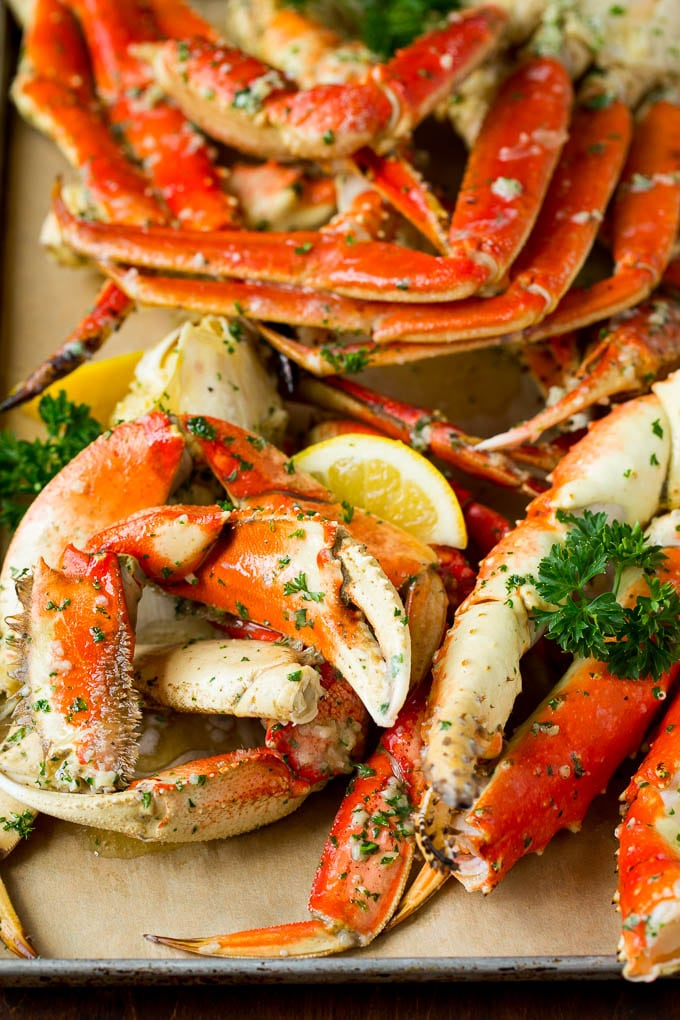 A tray of crab legs seasoned with garlic and herbs.