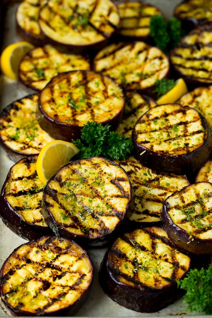 Grilled eggplant topped with fresh parsley on a sheet pan.