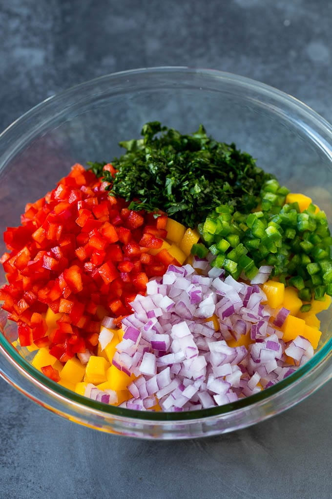 Diced mango, peppers, red onion and cilantro in a bowl.