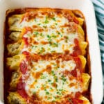 A dish of baked manicotti pasta topped with melted cheese and parsley.