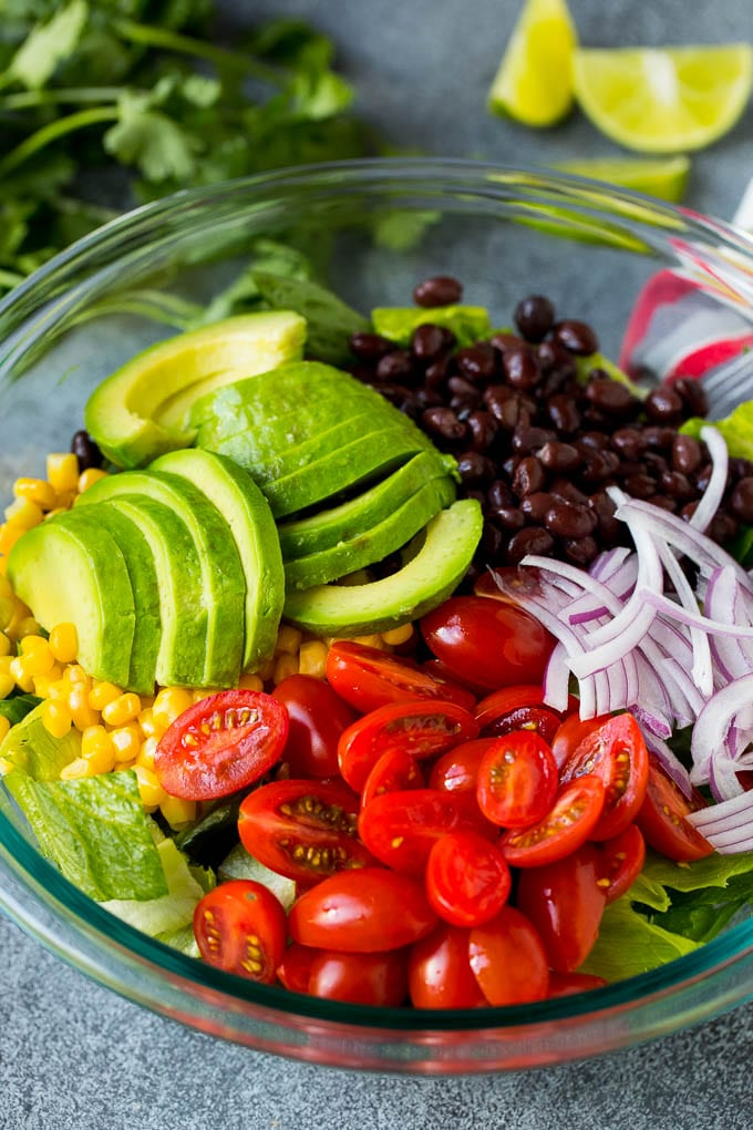 Lettuce, tomatoes, onion, corn, avocado and black beans in a bowl.