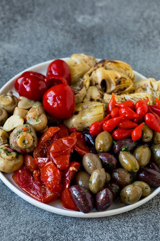 A plate of olives, peppers and grilled artichokes.