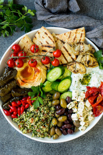 A mezze platter filled with dips, pita bread, vegetables, olives and cheese.