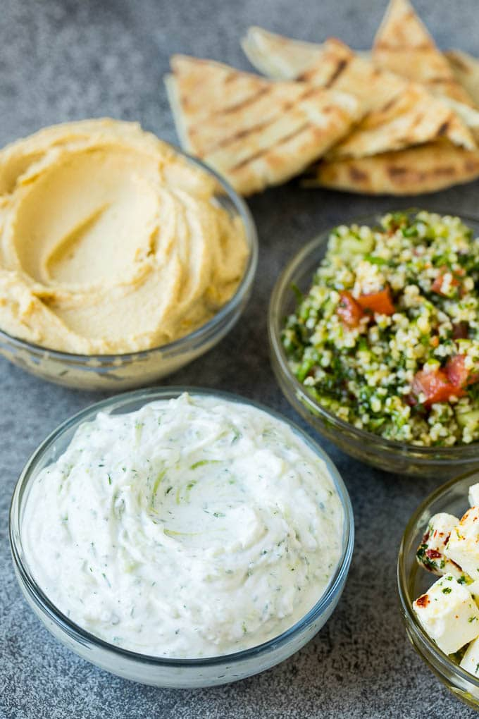 Bowls of hummus, tzatziki and tabbouleh.