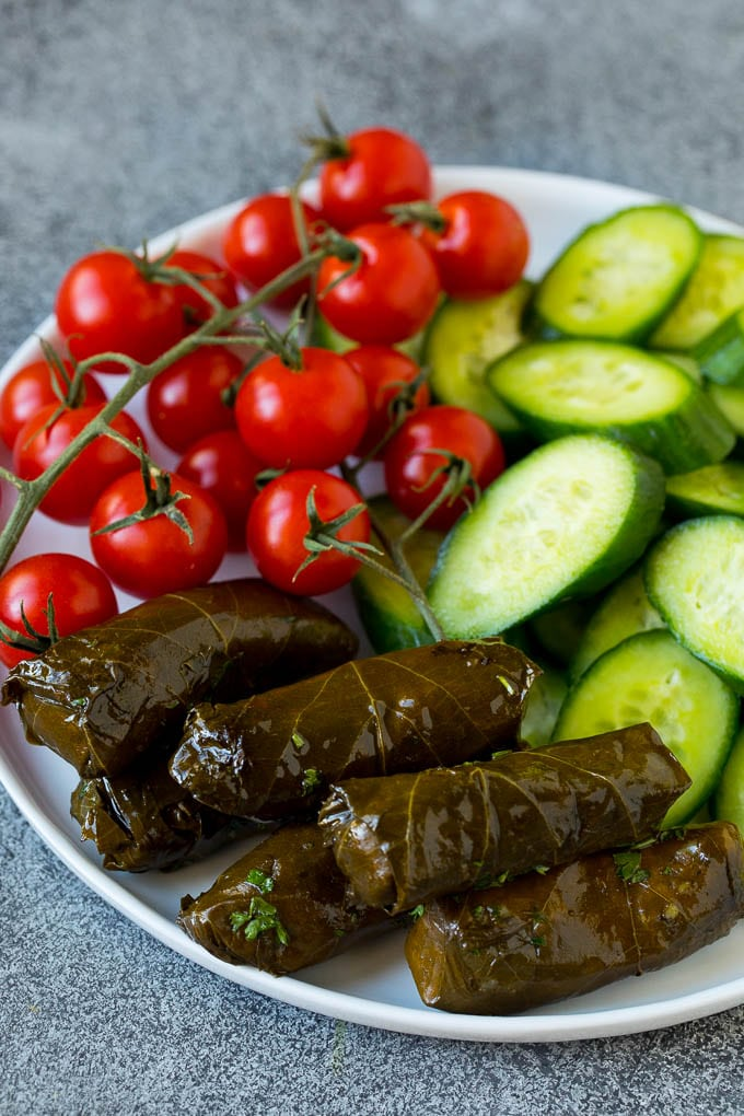 A plate of cherry tomatoes, cucumber slices and dolmas.