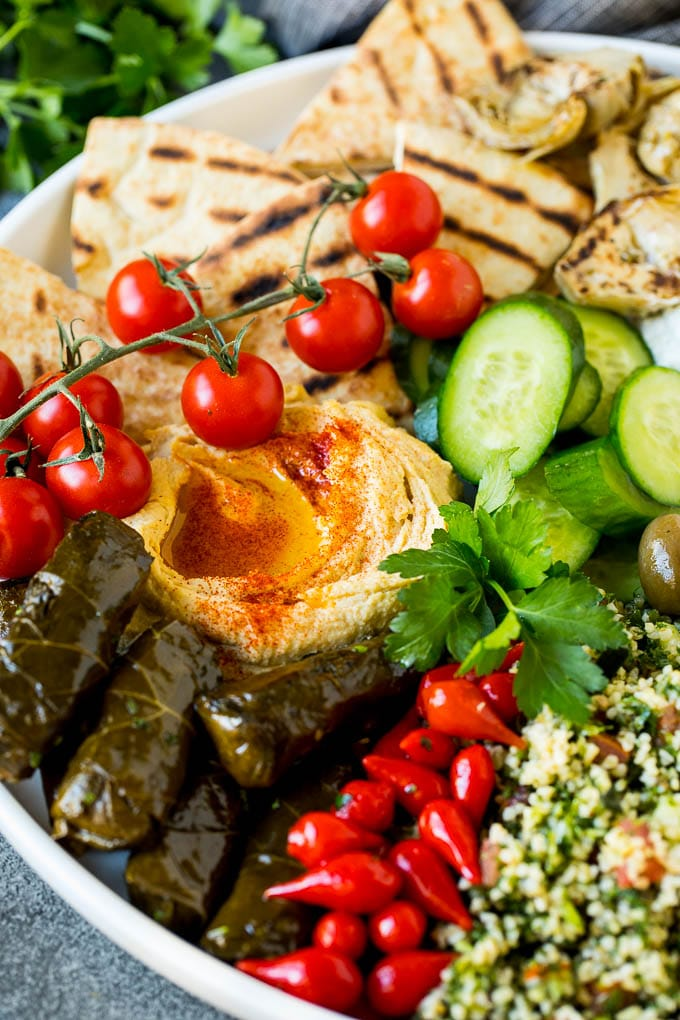 A Mediterranean mezze platter with hummus, dolmas and vegetables.