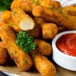 Mozzarella sticks served with a side of marinara sauce.