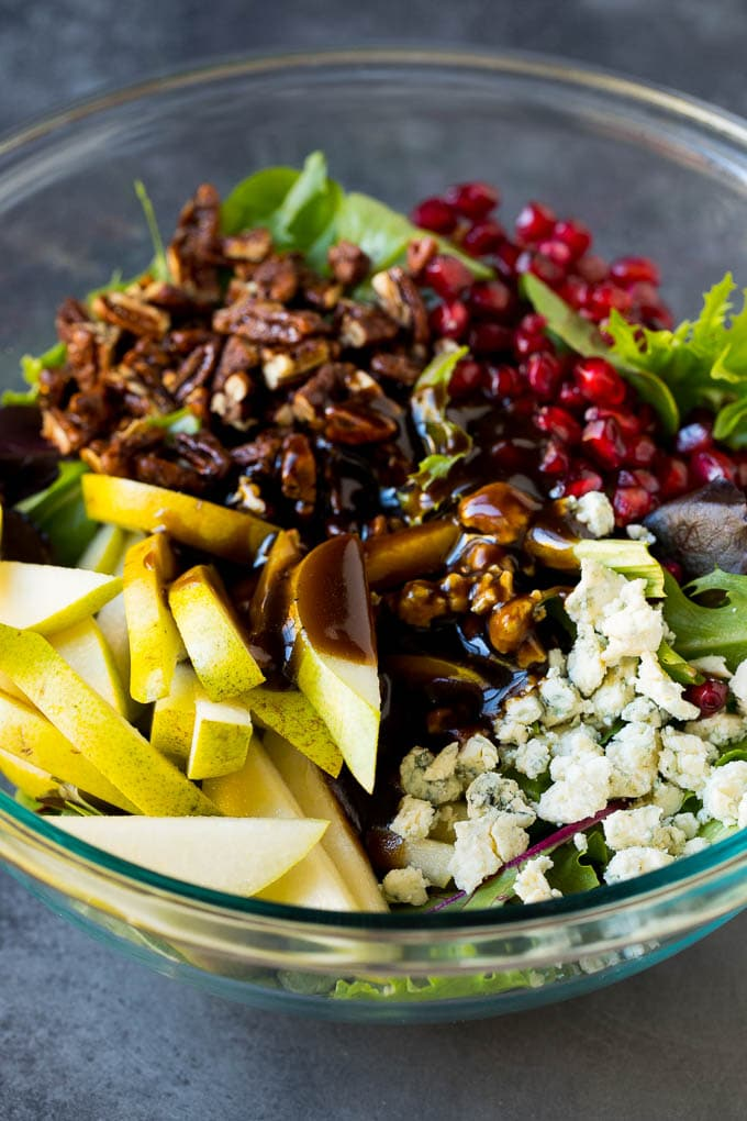 Balsamic dressing poured over a bowl of mixed greens, sliced pears and pomegranate seeds.