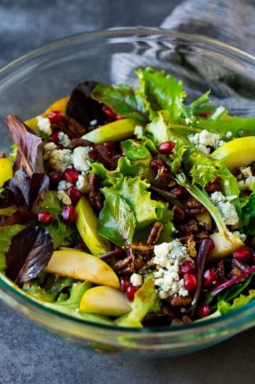 A bowl of pear salad with pomegranate, blue cheese and candied pecans.