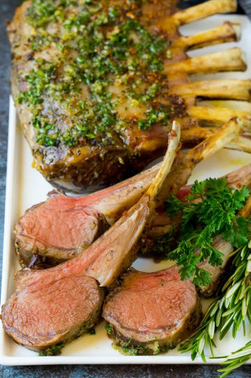 A platter of rack of lamb garnished with fresh herbs.