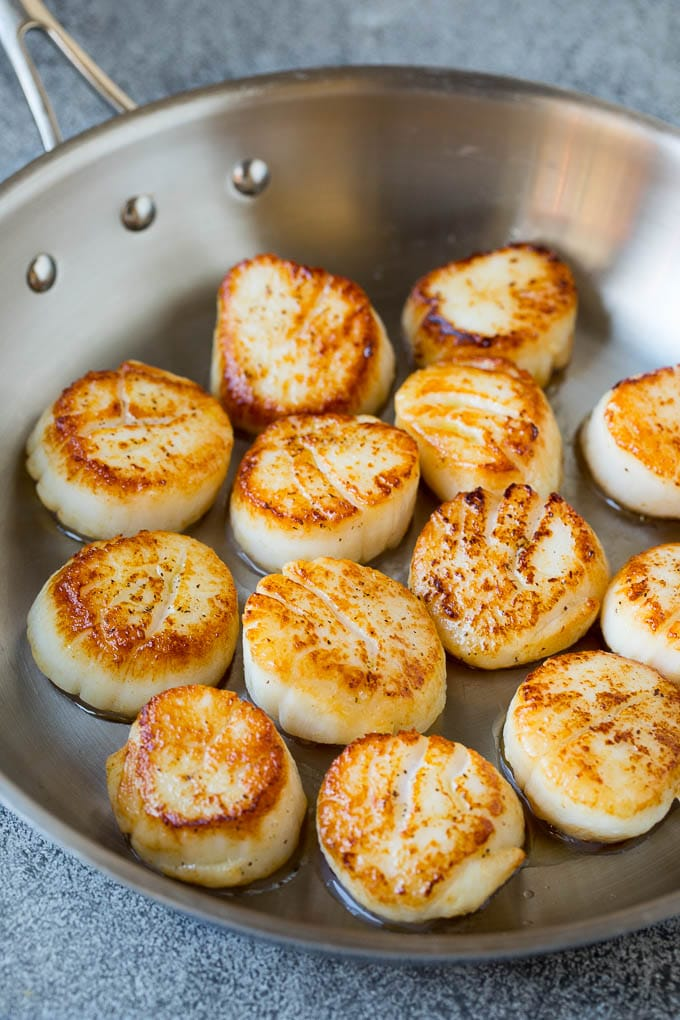Scallops cooked to golden brown in a pan.