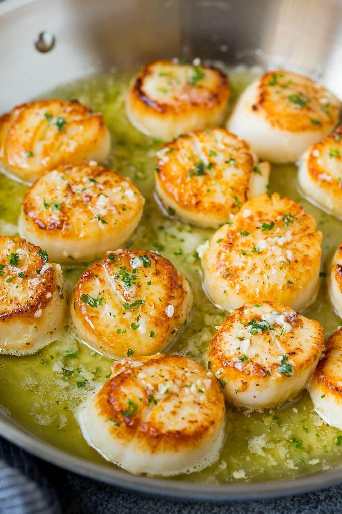A pan of scallops in garlic butter.