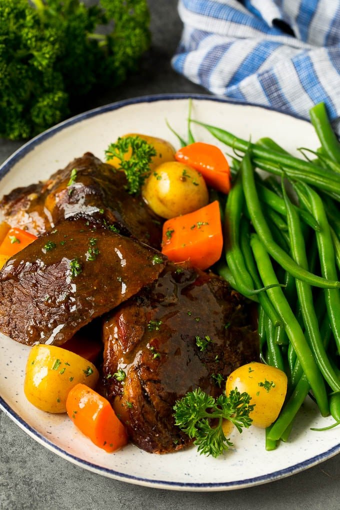 Slow cooker pot roast served with carrots, potatoes and green beans.