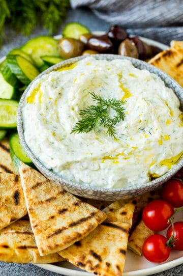 A bowl of tzatziki served with pita bread and vegetables.