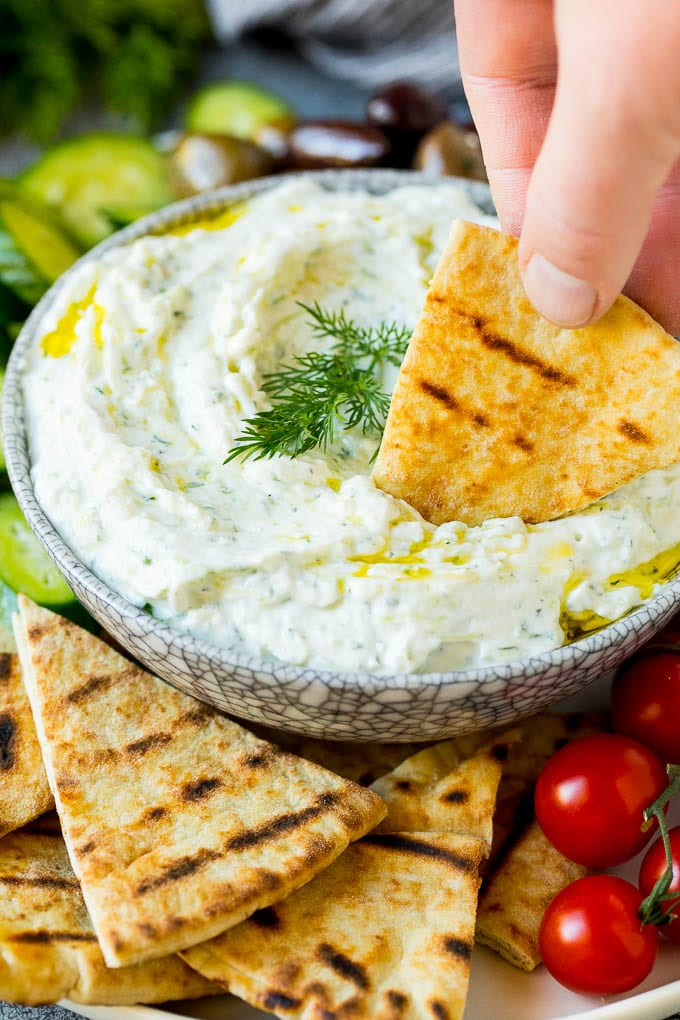 A hand dipping pita bread into a bowl of tzatziki.