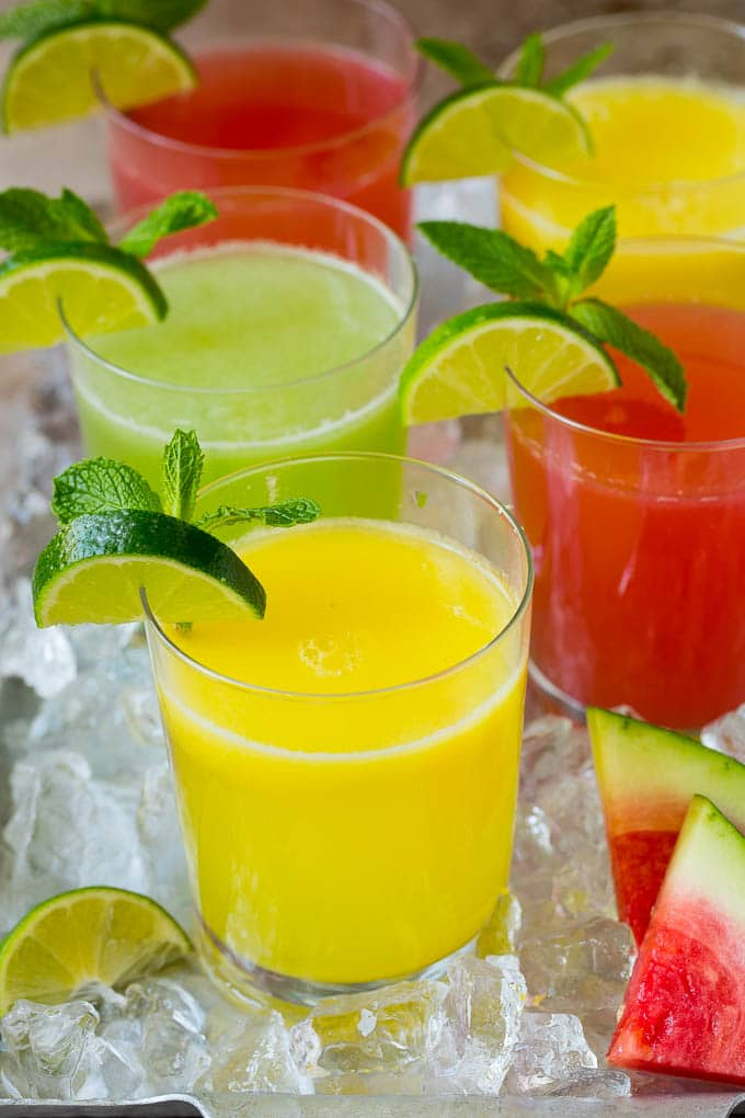 Cups of agua fresca in assorted fruit flavors.