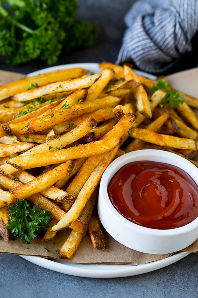 A plate of baked french fries served with ketchup.