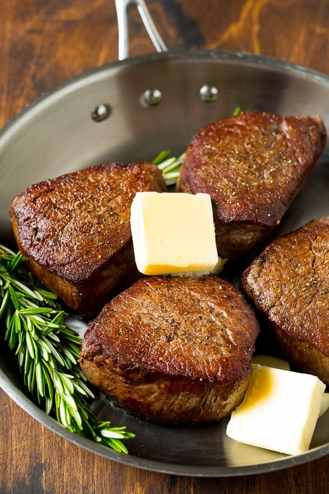 Cooked steaks with pats of butter, rosemary and garlic.