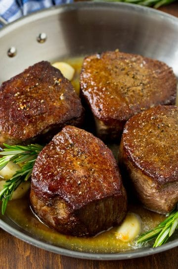 Filet mignon steaks topped with garlic butter and garnished with fresh rosemary.