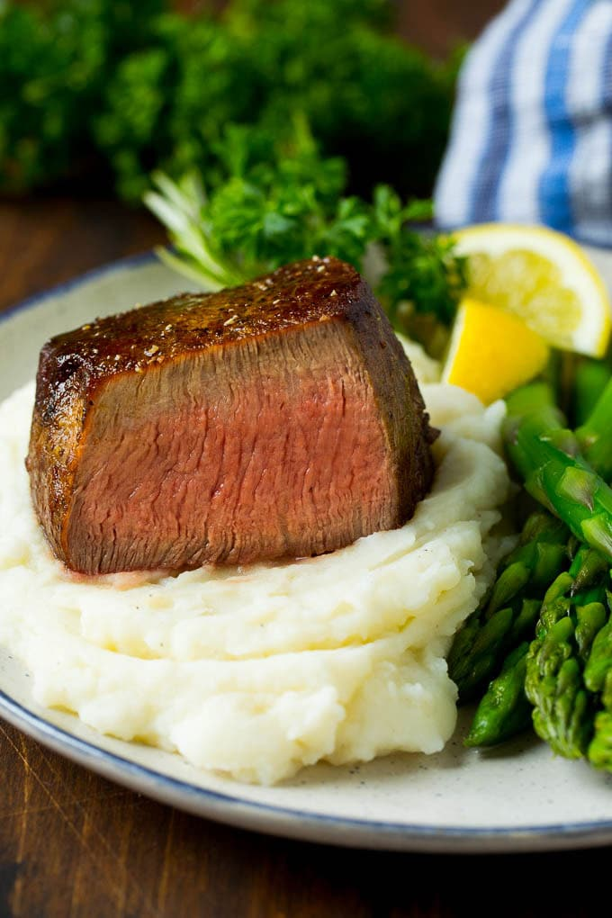 A cut filet mignon steak served with mashed potatoes and asparagus.