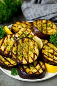 A serving plate of grilled eggplant served with parsley and lemon wedges.