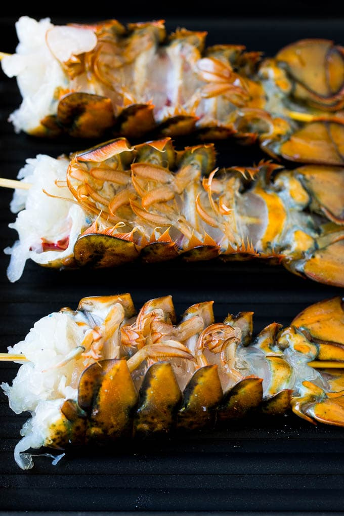 Lobster tails upside down on a grill pan.