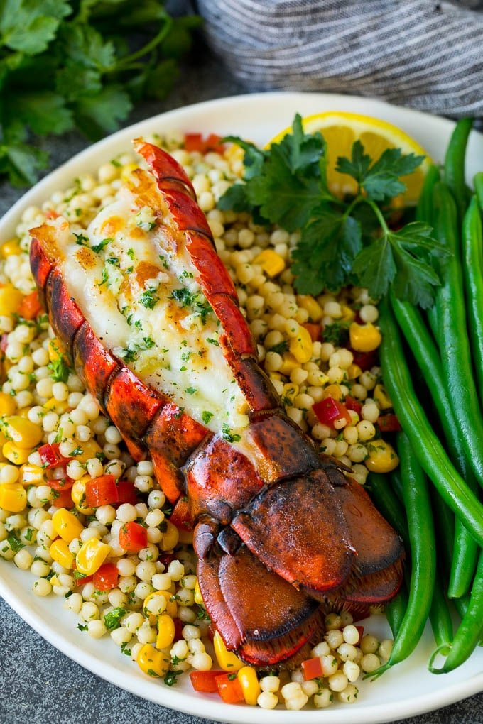 Grilled lobster tail served with couscous and green beans.