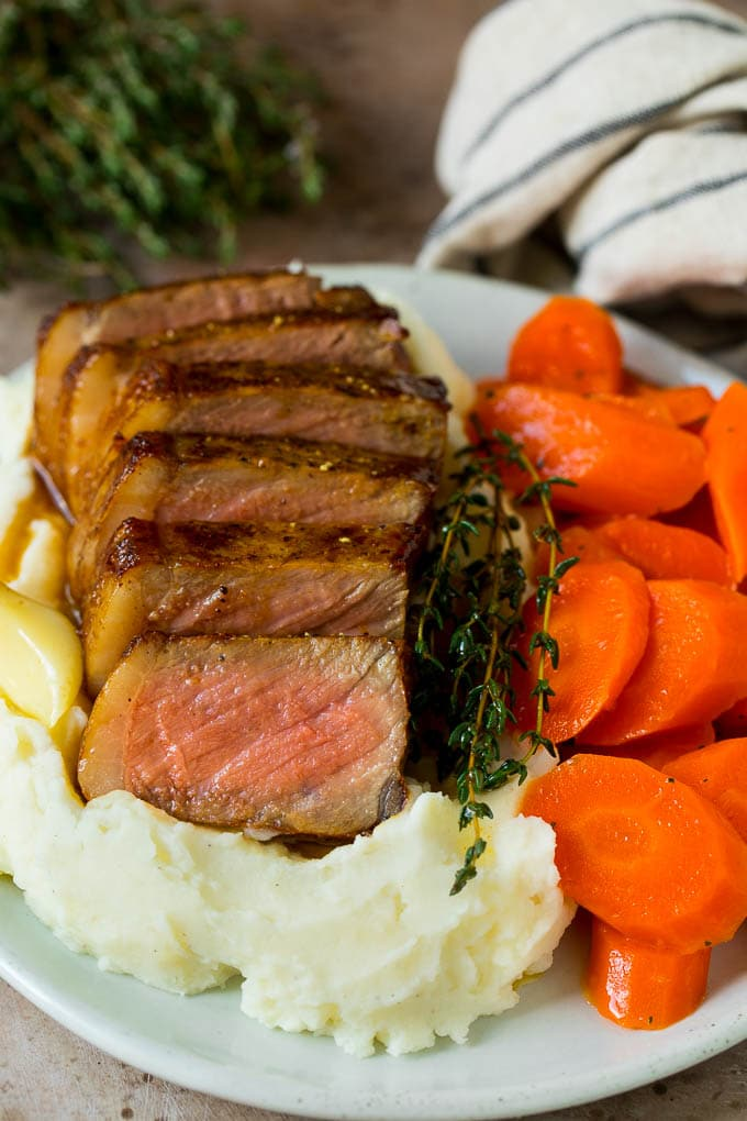 Sliced New York strip steak served with mashed potatoes and carrots.