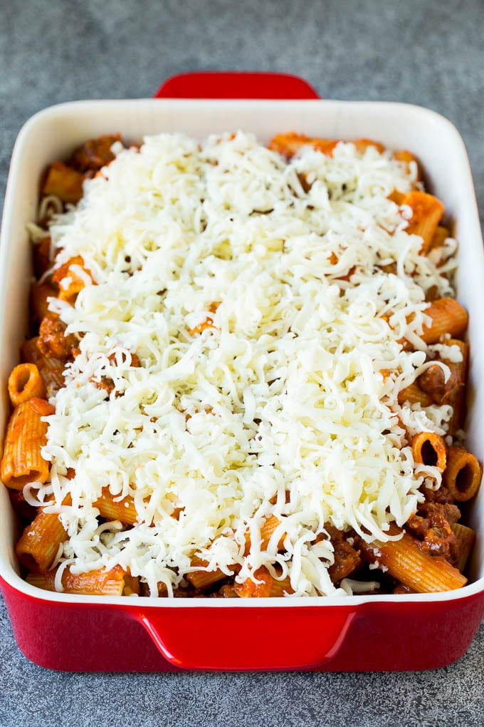 A dish of rigatoni tossed in meat sauce and topped with shredded cheese.