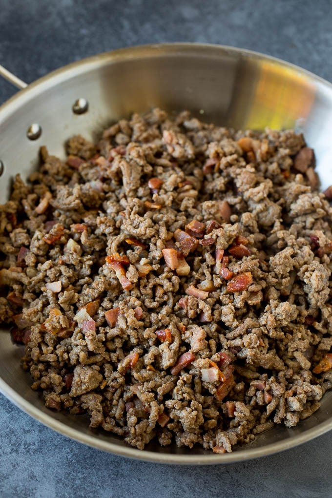 Ground beef and pancetta cooked in a pan.