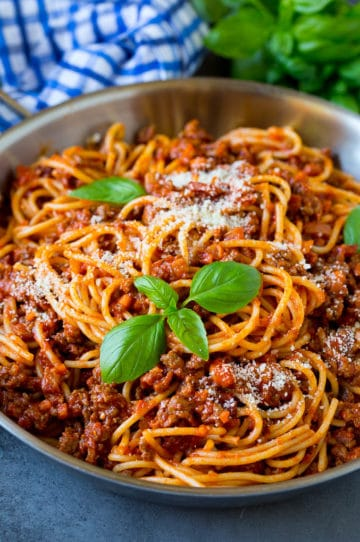 A pan of pasta bolognese garnished with basil sprigs and parmesan cheese.