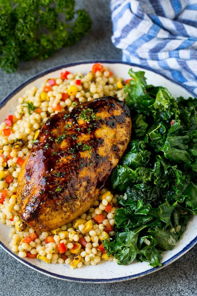 Grilled chicken served with a side of sauteed kale.