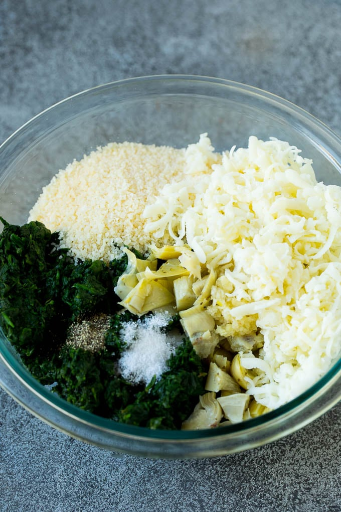 Spinach, artichokes, three types of cheese and seasonings in a bowl.
