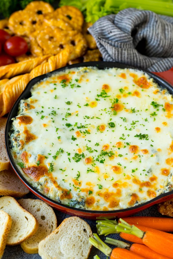 Spinach artichoke dip served with bread, pretzels and vegetables.
