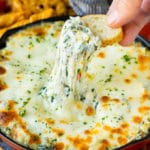 A hand scooping out a portion of spinach artichoke dip.