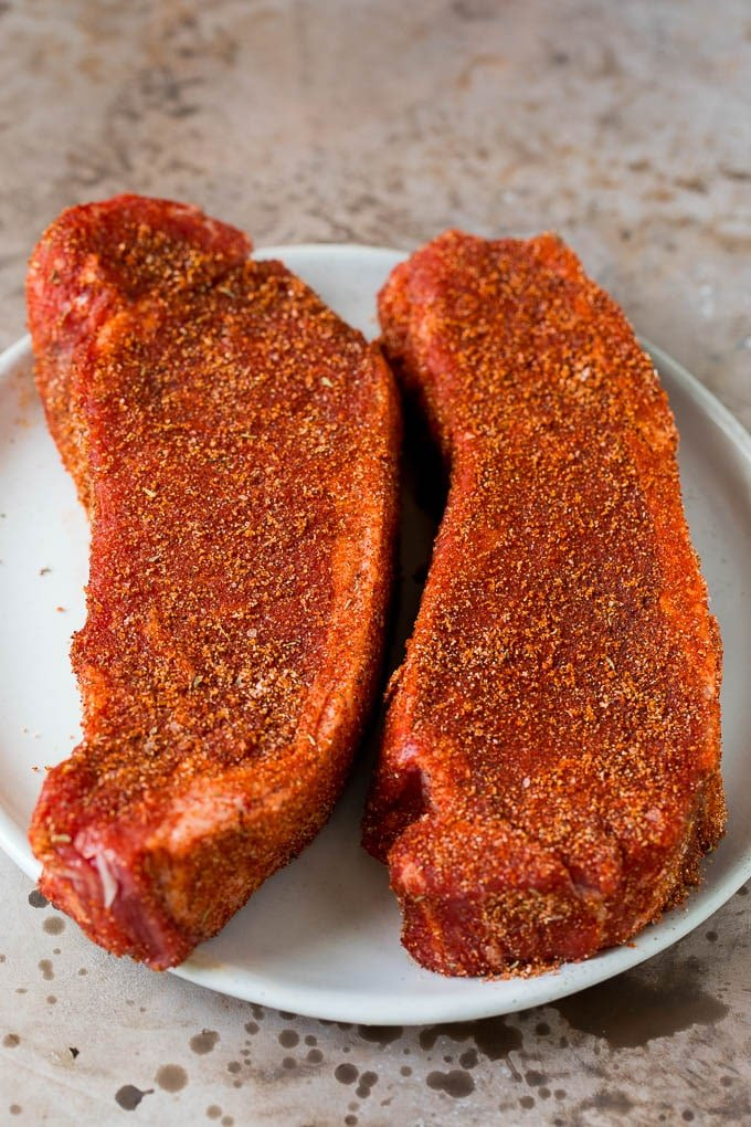Steaks coated in seasoning on a plate.