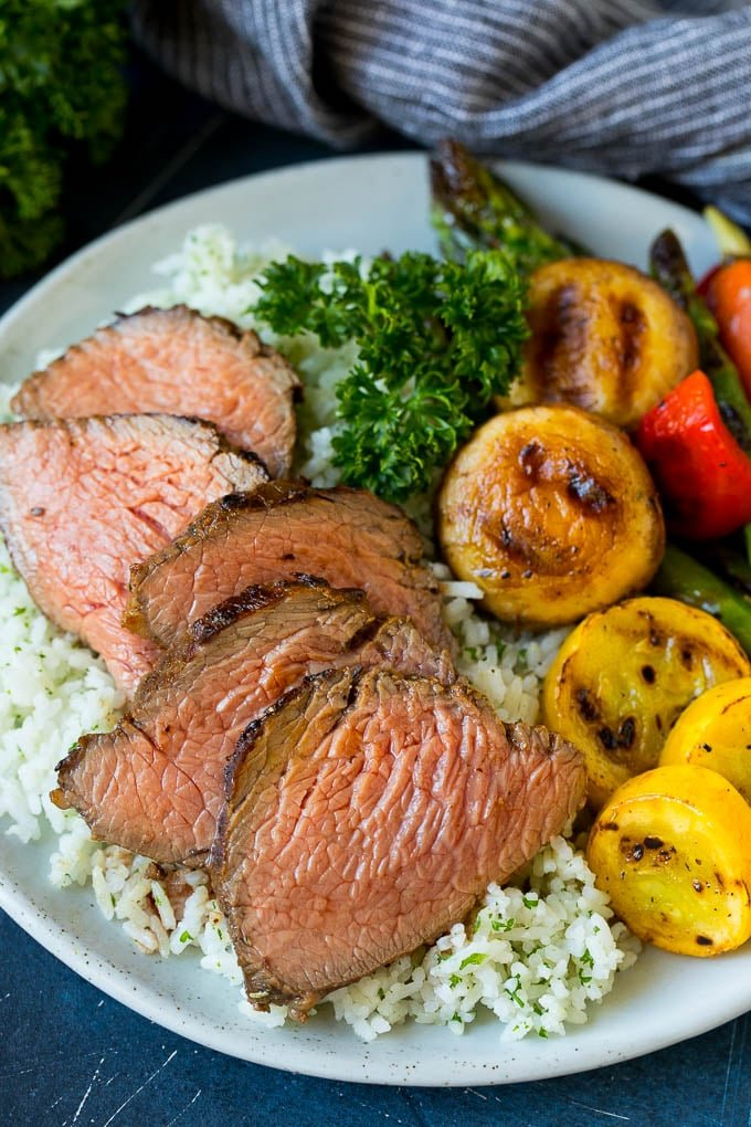 Sliced meat cooked in tri tip marinade over rice with vegetables.