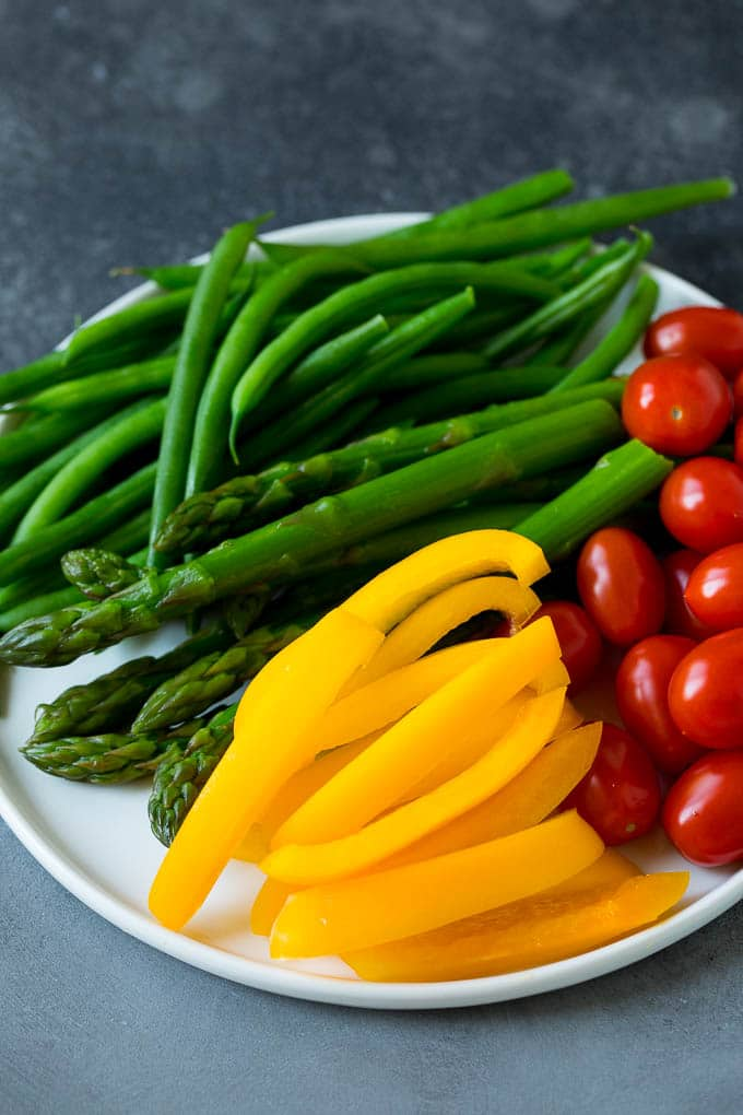 Bell peppers, asparagus, tomatoes and green beans on a plate.