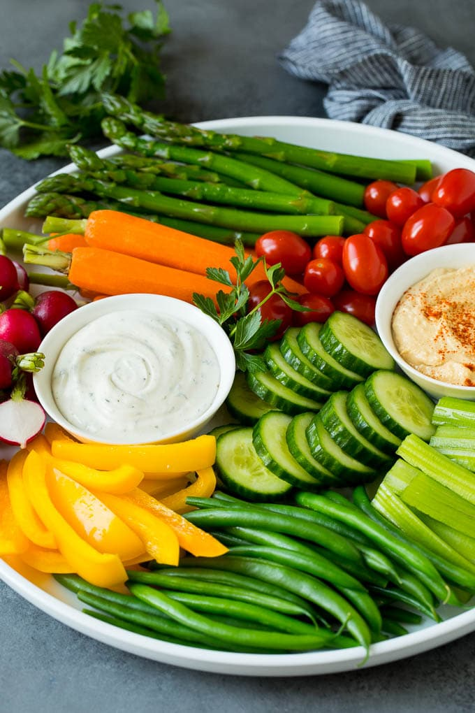 A veggie tray filled with fresh vegetables and two types of dip.