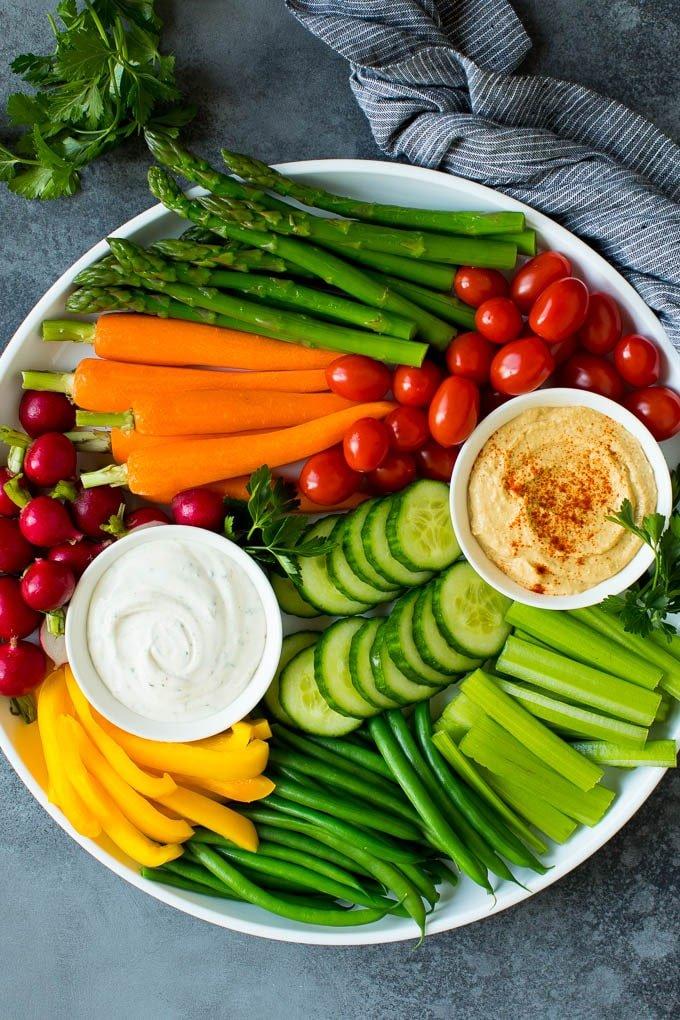 A large veggie tray with assorted fresh and steamed vegetables, ranch dip and hummus.