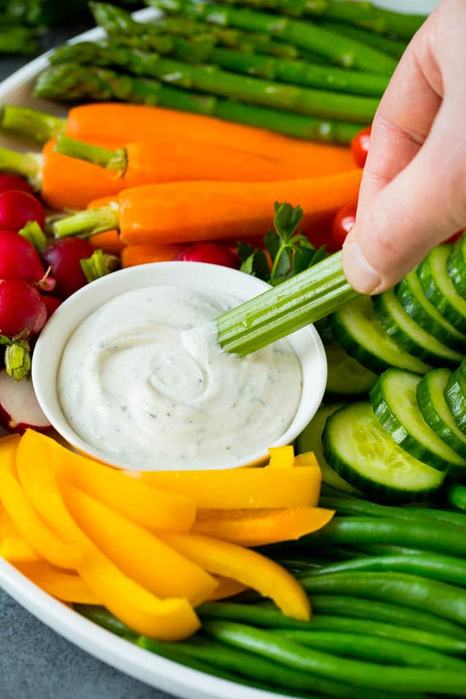 A hand dipping celery into ranch sauce.
