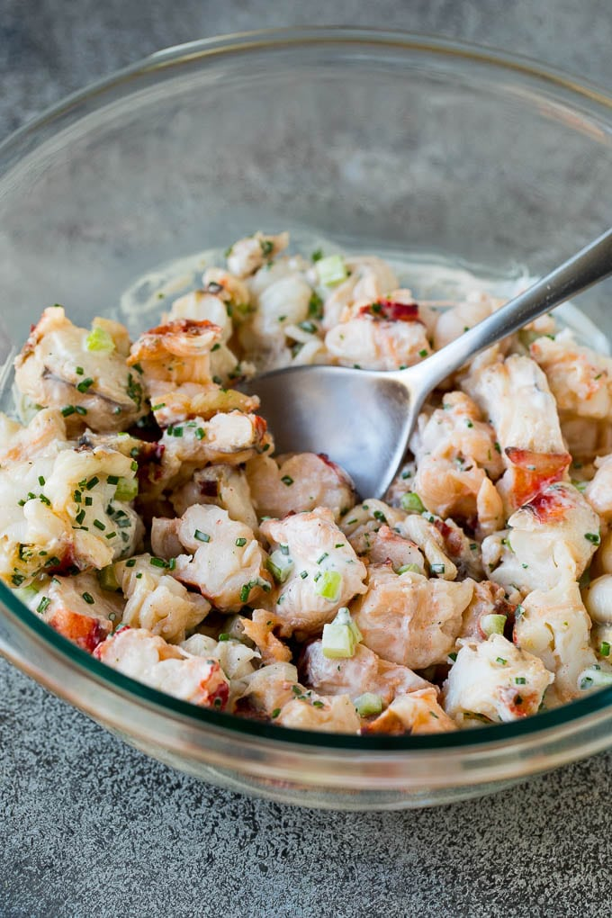 A mixing bowl filled with lobster tossed in dressing.